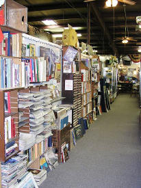 Magazines, sheet music & various paper items in the racks line the walkway/asile of John whiting's Old Paper Shop inside Antique Village Mall.